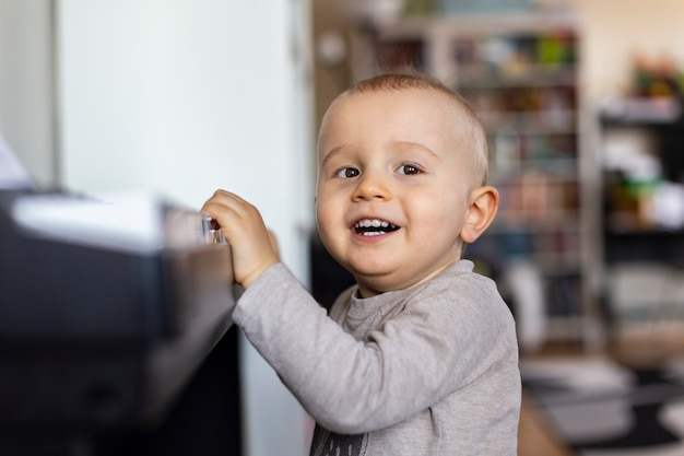 A toddler boy is standing at the piano and smiling.