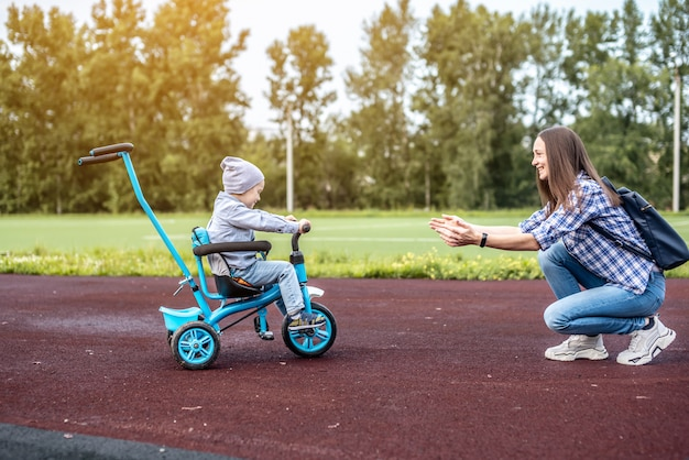 유아 소년은 어린이 세발 자전거를 타고 어머니에게 성공적으로 가고 있습니다.