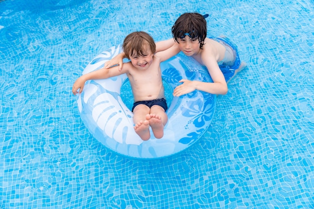 여름에 수영장에서 풍선 링에 누워 동생과 노는 유아 소년. 아이들은 휴일을 즐깁니다.