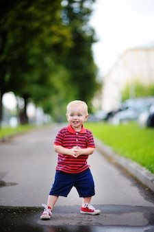 Toddler boy playing in the city at the spring or summer day