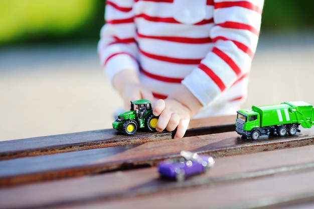 Toddler boy playing with toy cars outdoors at warm summer day