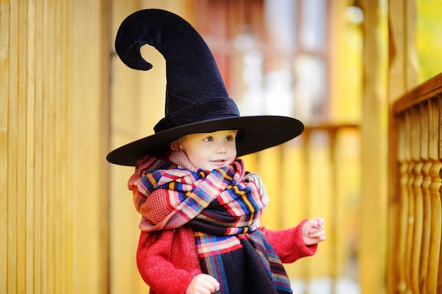 Toddler boy in pointed hat playing outdoors. little wizard