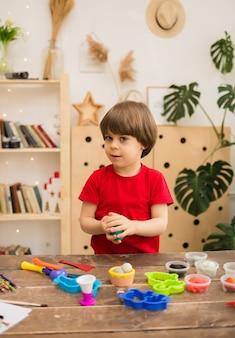 유아 소년은 방에있는 테이블에서 플라스틱으로 조각합니다.