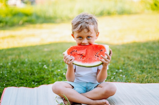 Toddler boy sit on the grass and eat red ripe watermelon. childhood, immunity, happiness, healthy snack