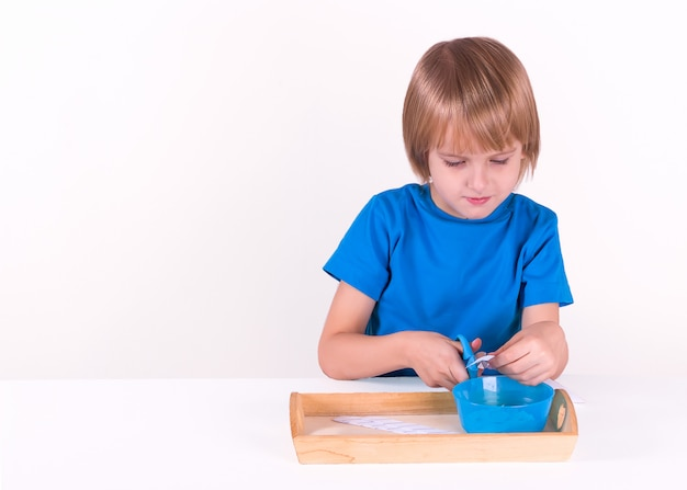 Toddler boy sits by the table with a tray of montessori materials for a lesson of practical life on a white background