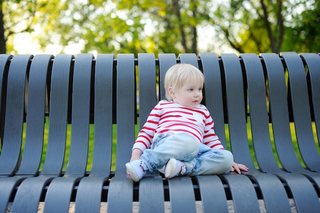 Toddler boy sitting on a bench outdoors