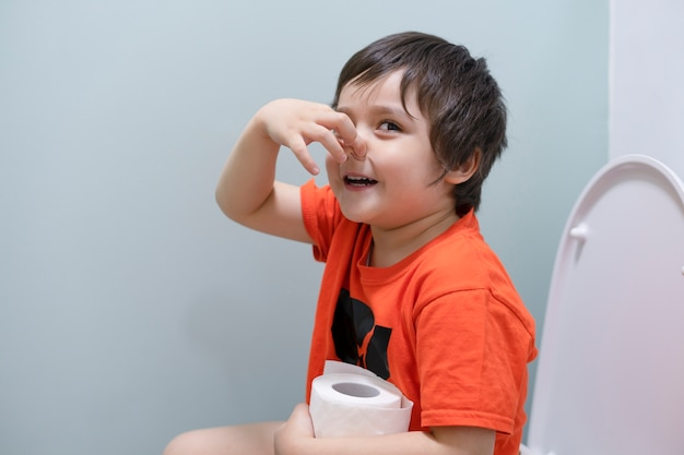 Toddler boy sitting in the toilet and covers his nose from the smell