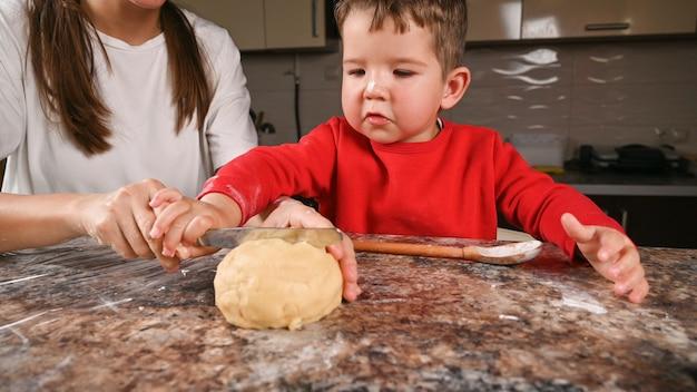 彼の母親と一緒の幼児の男の子はナイフで生地をカットします