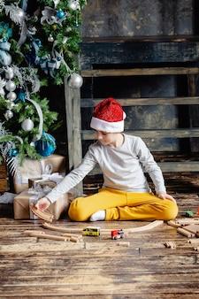 산타 모자 철도를 구축 하 고 크리스마스 트리 아래 장난감 기차를 가지고 노는 유아 소년. 크리스마스 선물을 가진 아이. 크리스마스 때.