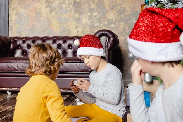철도를 구축 하 고 크리스마스 트리 아래 장난감 기차를 가지고 노는 유아 소년. 크리스마스 선물을 가진 아이. 크리스마스 때.