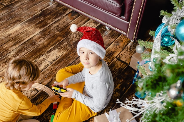 Toddler boys building railway and playing with toy train under christmas tree.