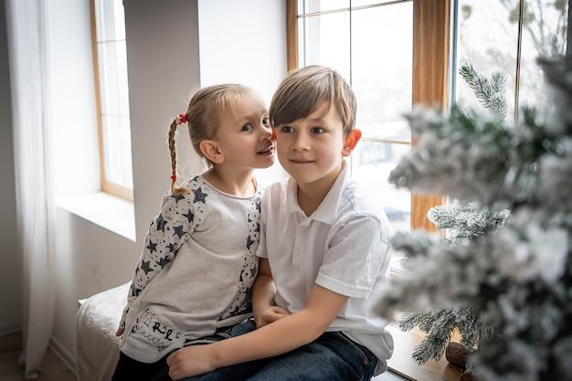 Дети младшего возраста, братья и сестры, дети сидят перед большим окном, прислонившись к нему, глядя на ночное небо и санта-клауса, счастливого рождества с новым годом