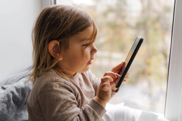 自宅で電話を使用している幼児の子供
