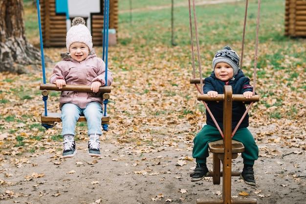 Дети малыша, раскачивающиеся в парке