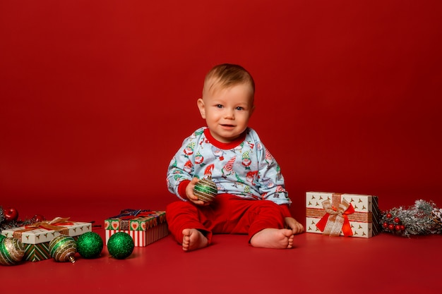Toddler in christmas pajamas on red background, space for text