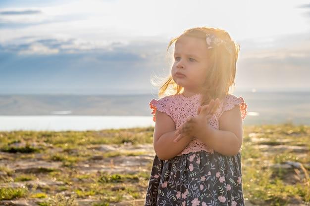 美しいピンクとブルのドレスで幼児のかわいい女の子が彼女の手をこすり、目をそらします。