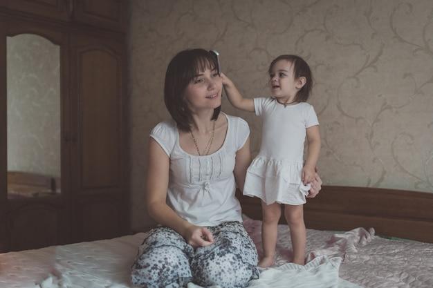 Малышка расчесывает образ жизни молодой темноволосой мамы, пастельные тона,