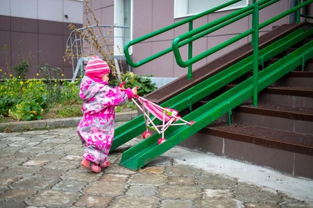 유아는 계단 경사로를 따라 장난감 유모차를 끌고 있습니다.