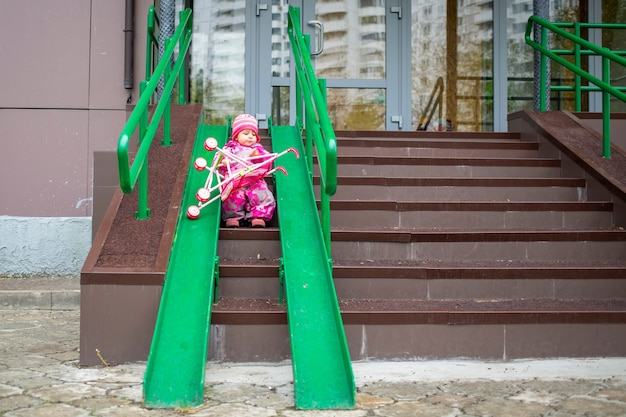 Toddler drags a toy stroller along the ramp of the stairs