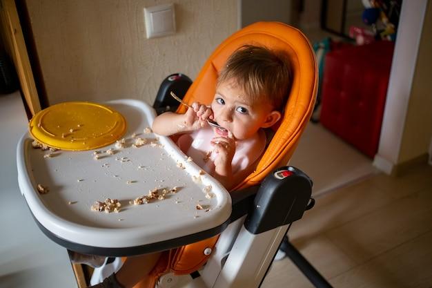 Малыш ест грязно в стульчике для кормления дома