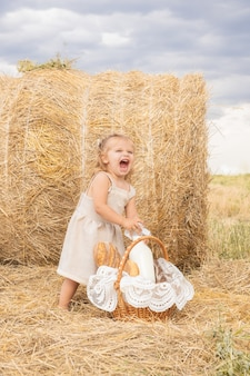 Toddler girl blond in linen dress takes bottle of milk from the bread basket