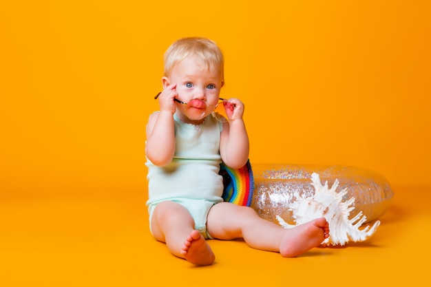 Toddler girl in blue bodysuit and swimming circle sits on a yellow wall