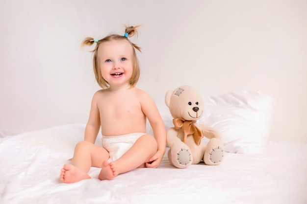 Toddler girl in diapers sits with toy bear on bed at home