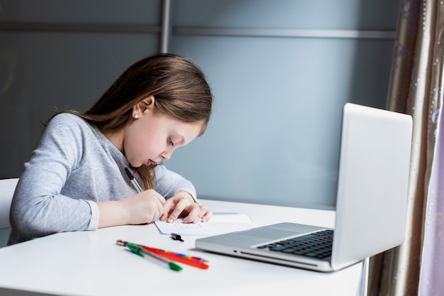 Маленькая девочка делает домашнее задание с ноутбуком на белом столе дома
