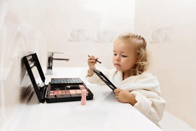 Toddler girl doing makeup with eyeshadows in bathrobe