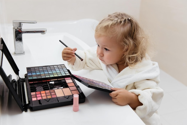 목욕 가운에 아이섀도우로 화장을 하는 유아 소녀