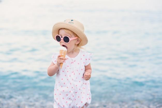 Малышка в летней одежде и розовых очках стоит на пляже, ест с большим удовольствием белое мороженое. счастливых летних каникул.