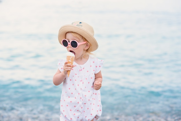 Toddler girl dressed in summer clothes and pink sunglasses stands on the beach eats with great pleasure white ice cream. happy summer vacations.