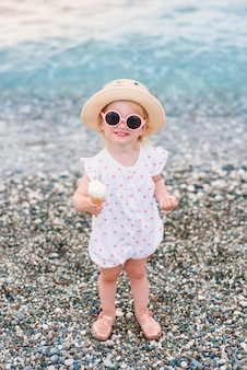 Toddler girl dressed in summer clothes, yellow hat and pink sunglasses stands on the beach eats white ice cream and looks at the camera.