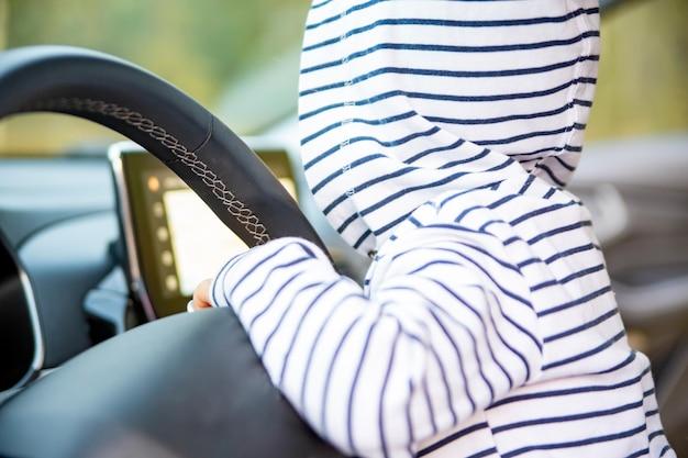 Toddler girl driving a modern car