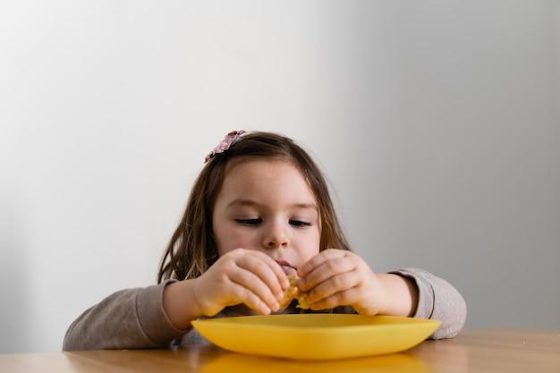 彼女の手で家でパンやパイを食べる幼児の女の子。空腹の子供。不健康な食事。悪いテーブル