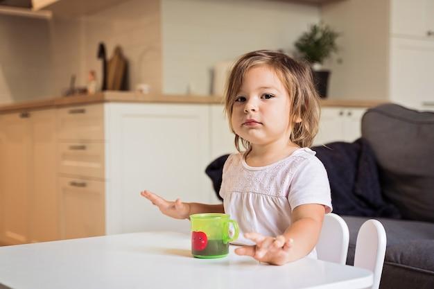 쿠키와 음료 주스를 먹는 유아 소녀. 어린 이용 간식. 고품질 4k 영상