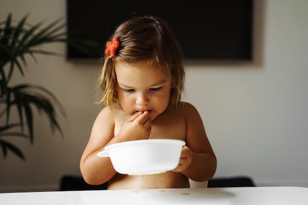 Девочка малыша есть печенье и пить сок. Premium Фотографии