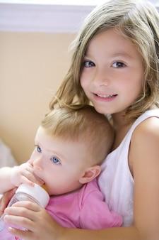 Toddler girl giving bottle of milk to baby sister