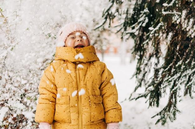 Девушка малыша счастлива со снежным днем зимой. игра на улице в рождественские каникулы