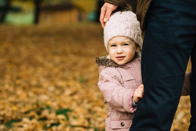 Toddler girl hiding behind adult leg