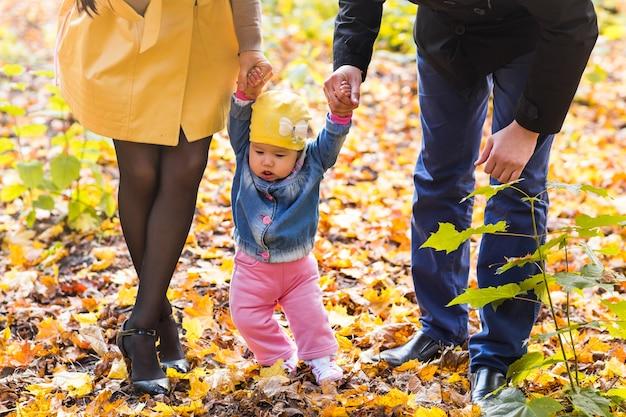 가을 날에 외부 그녀의 어머니와 아버지와 손을 잡고 유아 소녀