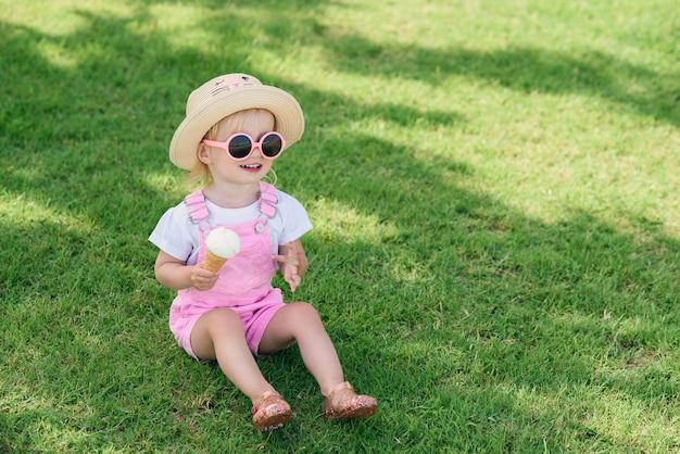 Малыш девочка в розовый летний комбинезон, шляпа и розовые очки сидит на зеленой траве с мороженым в руке и улыбается.
