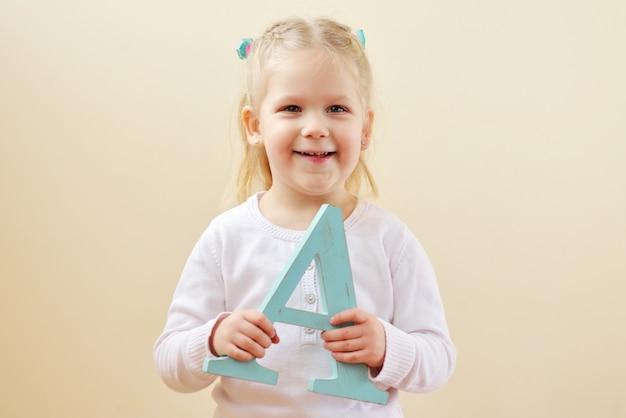 幼児の女の子は文字aで立っています