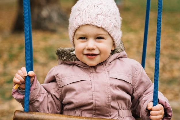 Toddler girl in knitted hat swinging in autumn garden