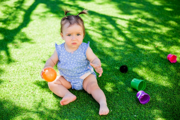 Девушка малыша играя игрушки напольные