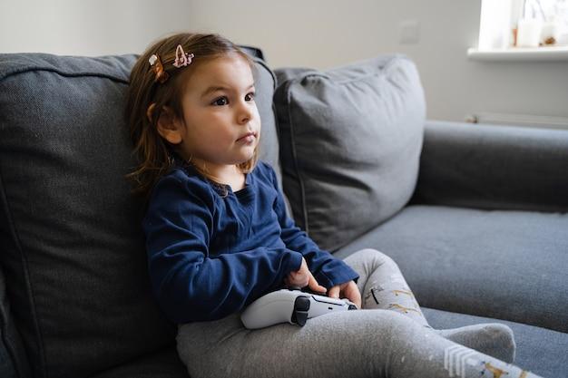 ソファの上のリビングルームで自宅でビデオゲームコンソールをプレイしている幼児の女の子。若いゲーマーの子供。