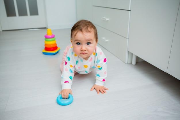 Малышка играет в развивающие игры дома. ребенок сидит на полу дома