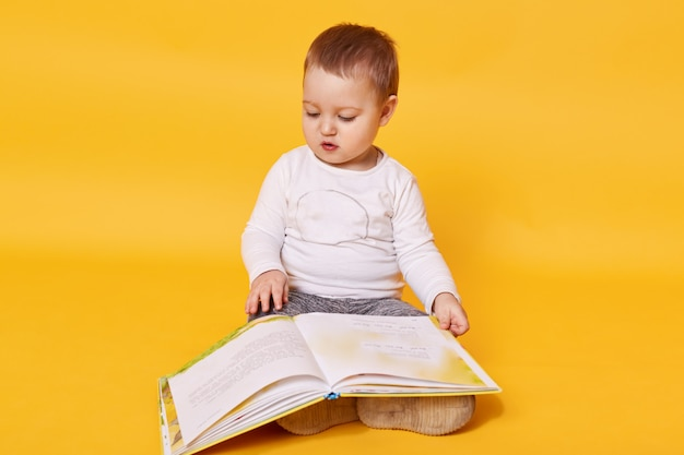 Toddler girl pretends to read book while sitting on floor, viewing pictures and turning pages, little girl looks concentrated