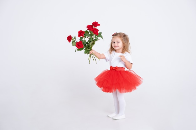 Toddler girl in red skirt and holding bouquet of roses on white background. valentine day concept.