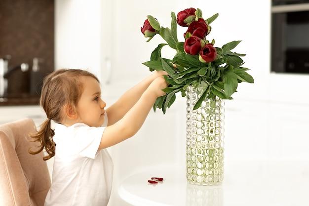 幼児の女の子は白いテーブルに座って、赤い牡丹の花の花束の世話をします